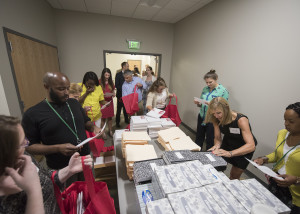 Volunteers and corps members work together to assemble classroom kits of school supplies.